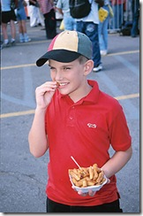 Boy eating French fires at fair uid 1174394
