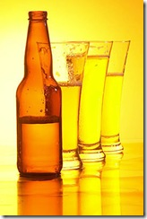 Brown beer bottle beside glasses of beer uid 1180099