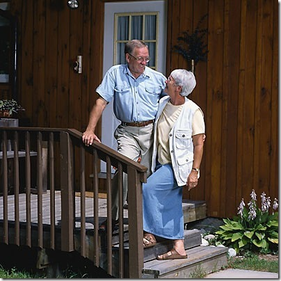 elderly couple in front of house uid 1187314